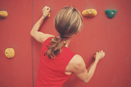 scaling: A young woman is scaling a bouldering wall Stock Photo