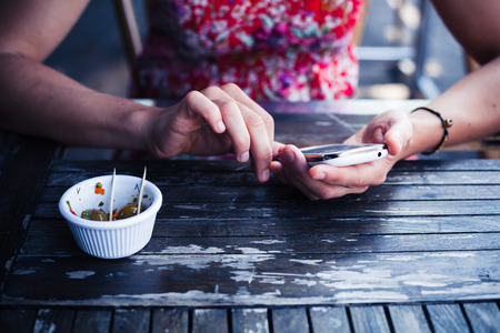 A young woman is using her smart phone at a table outside photo