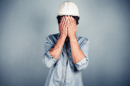 A blue collar worker wearing a hardhat is covering his face with his hands photo