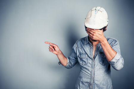 A blue collar worker covering his face is pointing photo