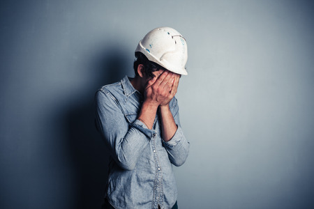 An upset blue collar worker is burying his face in his hands photo