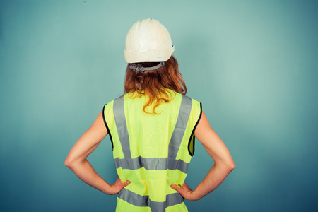 A young female engineer is wearing a high vis vest and a hardhat photo