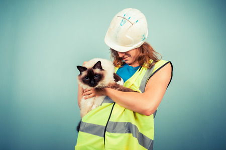 A young female builder is holding a cat photo