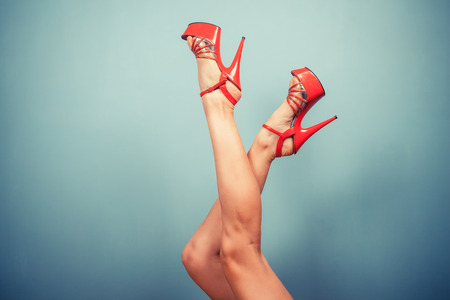 Sexy female legs wearing stripper heels against a blue background