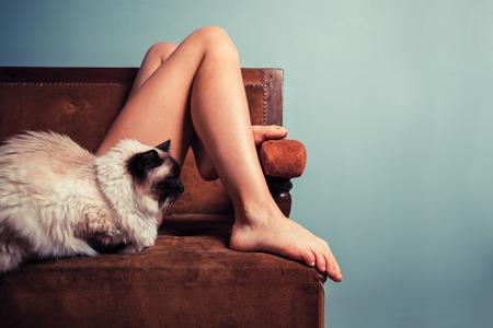jeune fille: Une jeune femme se d�tend sur un canap� avec un chat Banque d'images