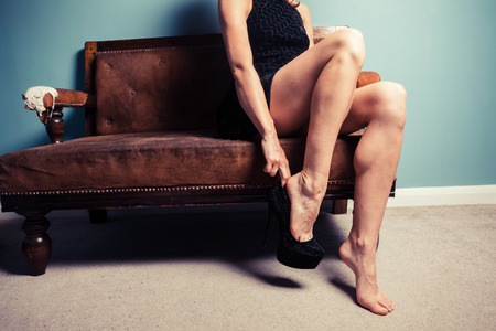 A sexy young woman is sitting on a sofa and is putting on high heel shoes