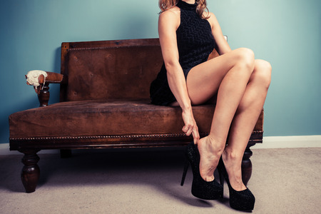 high heel shoes: A sexy young woman is sitting on a sofa and is putting on high heel shoes