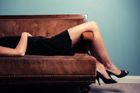 Une jeune femme sexy en talons hauts et robe de soirée est allongée sur un canapé Banque d'images - 31956816