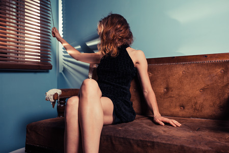 femme fatale: A sexy young woman is sitting on a sofa by the window Stock Photo