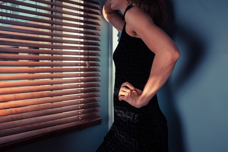 An elegant young woman is standing by a window and looking through the blinds Stock Photo