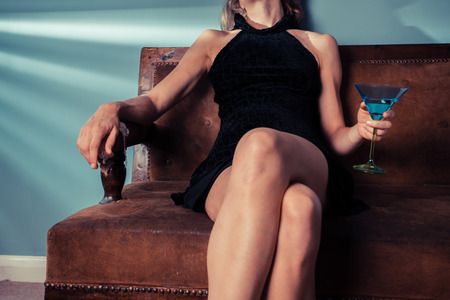 An elegant young woman is sitting on a safo and is drinking from a cocktail glass photo