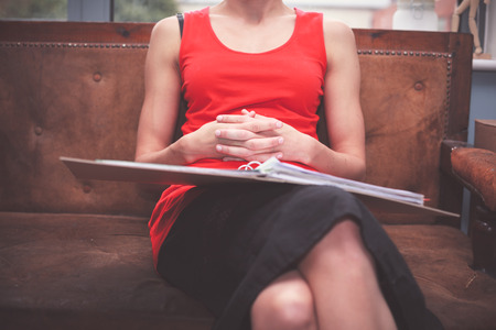 work from home: A young woman is sitting on a sofa with a ring binder filled with documents