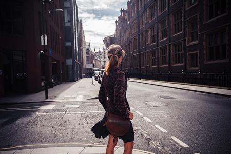 若い女性が通りを歩いてとアーキテクチャを見ています。