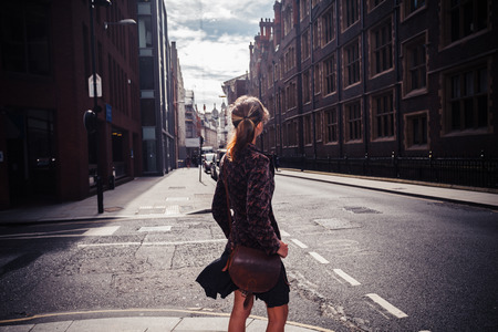 A young woman is walking in the street and is looking at the architecture Stockfoto