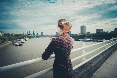 woman street: A young woman is standing on a bridge in the city and is admiring the skyline Stock Photo