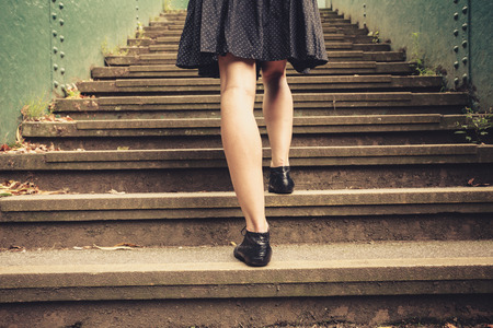 woman stairs: A young woman is walking up stairs outside in a park
