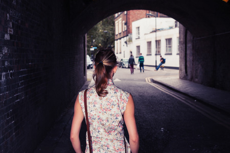 dark alley: A young woman is standing in a tunnel Stock Photo