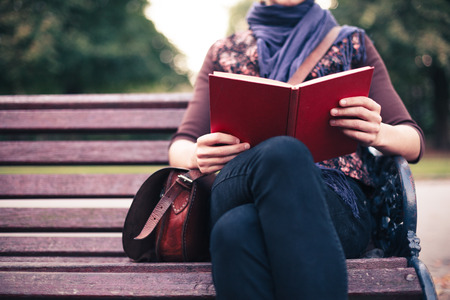 A young woman is sitting on a park bench and is reading a book