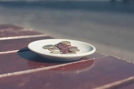 tipping: Coins on a saucer outside on a cafe table