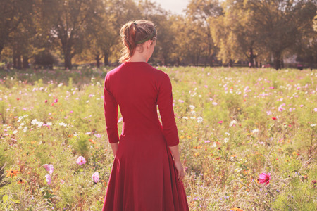 A young woman wearing a red dress is standing in a meadow at sunset photo