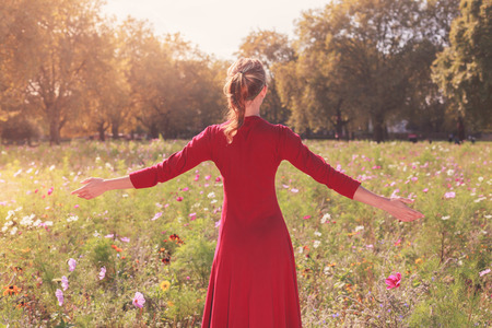 A happy young woman is raising her arms in a meadow on a sunny day photo
