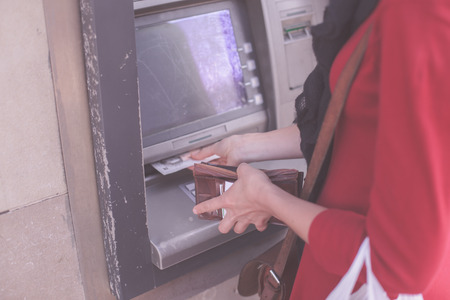 A young woman is withdrawing money from an ATM photo