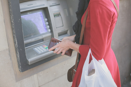 automatic teller machine: A young woman is withdrawing money from an ATM