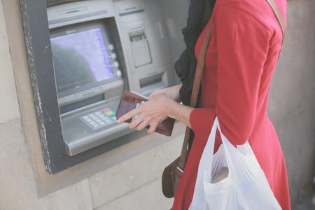 automatic transaction machine: Una mujer joven se est� retirando dinero de un cajero autom�tico
