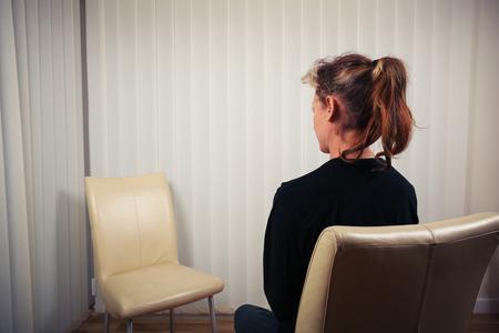 女性は椅子に座っていると彼女の医師やセラピストが待っています。