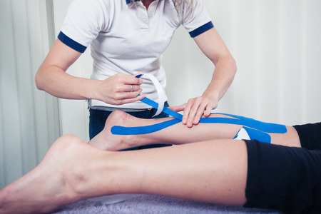 A physiotherapist is applying kinesio tape to a patients leg