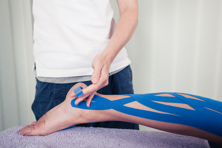 A physiotherapist is applying kinesio tape to a patients leg photo