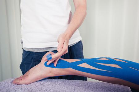Un physiothérapeute est d'appliquer du ruban Kinesio à la jambe d'un patient Banque d'images