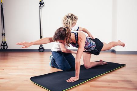 A therapist is correcting the technique of a woman exercising and stretching in a gym Archivio Fotografico