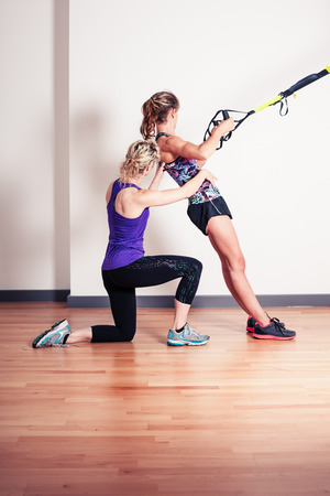 An athletic young woman is working out and is being corrected by her personal trainer