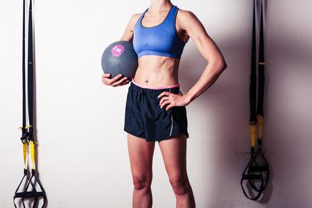 Eine sportliche junge Frau im Fitness-Studio stehen und hält einen Medizinball