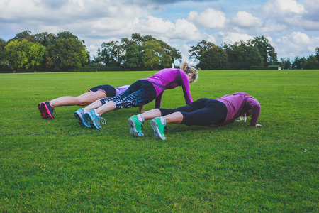 Three women are doing push ups on the grass in the park Foto de archivo