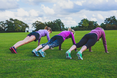 Three women are doing push ups on the grass in the park Stock Photo