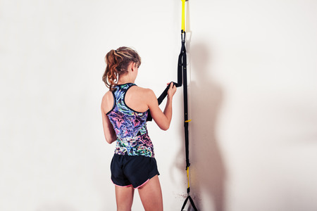 A fit young woman is studying a resistance band in the gym photo