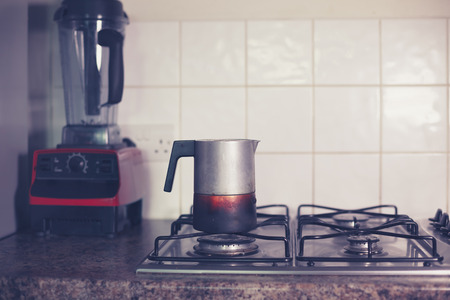 A moka pot on a stove with a blender in the background photo