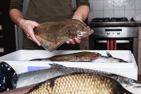 plaice: A young woman is in her kitchen and is holding a plaice with other types of fish in a box in front of her