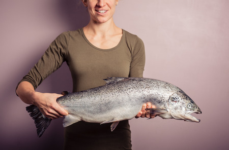 A young woman is posing with a large atlantic salmon in her hands photo