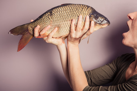 fresh fish: A young woman is posing with carp and is pulling silly faces