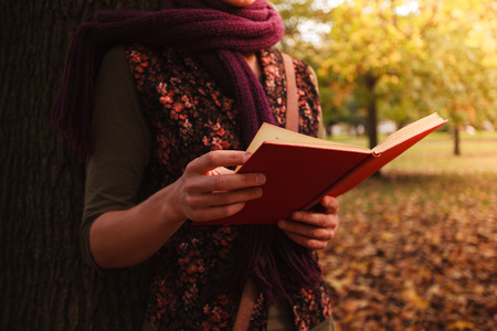 A young woman is leaning against a tree in the park and is reading a book on a sunny autumn day