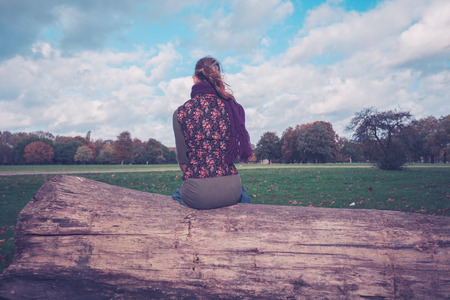 stitting: A young woman is stitting on a large fallen tree in the park on a sunny autumn day Stock Photo