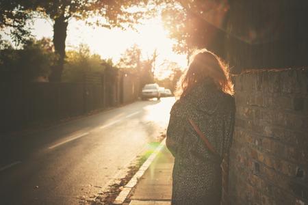 若い女性が街を歩いて秋の日の夕暮れに