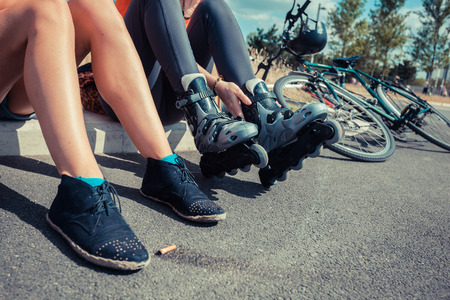 roller skate: Two young women are sitting by the roadside and one of them is putting on rollerskates Stock Photo