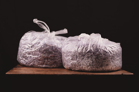 Two bags of shredded paper on a wooden table photo