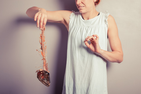A disgusted young woman is holding a fish skeleton