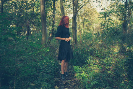 A young redhead woman is walking alone in the woods or enchanted forest Stock Photo
