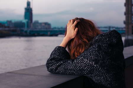 A sad woman is standing by a river in the city and is holding her head
